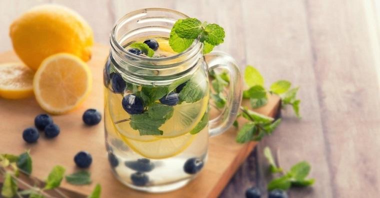 Ricette detox a base di acqua aromatizzata ai mirtilli e limone, servita in un barattolo di vetro