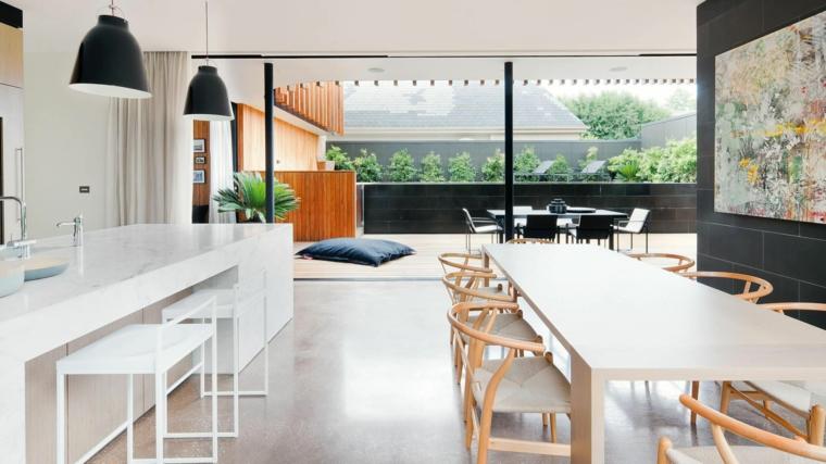 come arredare ambiente unico cucina soggiorno con mobili bianchi e moderni, una grande vetrata con bordi neri