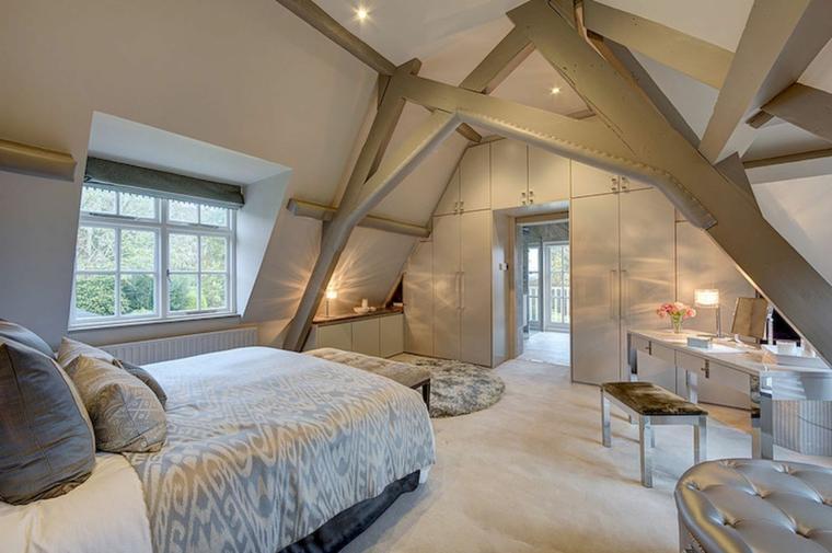 splendida camera da letto con travi a vista, mobili su misura, puff argento, mansarde moderne