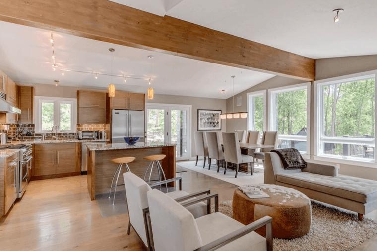 pavimento in parquet. soffitto ribassato, open space cucina soggiorno idee con mobili in legno e poltrone bianche