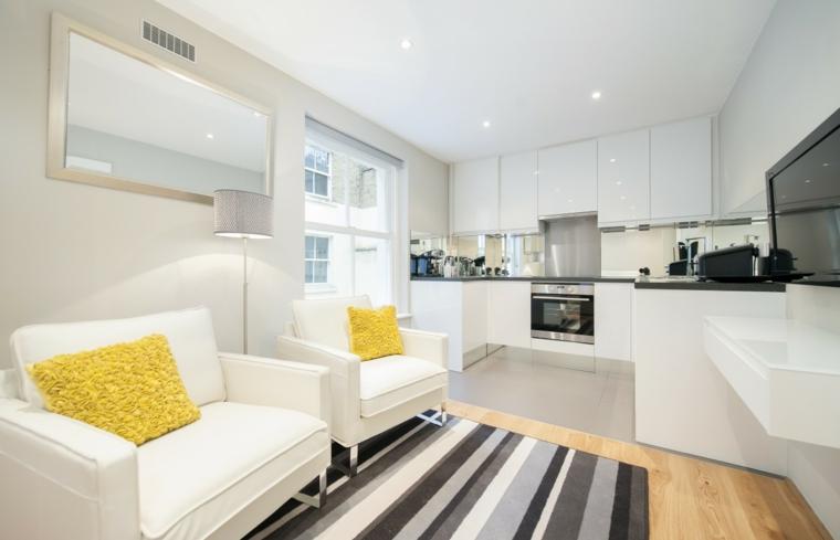 luminoso arredamento open space moderni, poltrone bianche e cuscini gialli. cucina a u bianca
