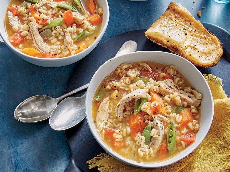 Pastina in una minestra di pollo con verdure, carote e fagiolini, pane bruschetta condita con olio