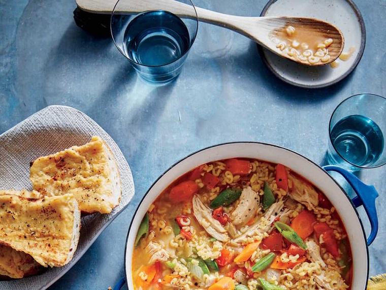 Minestra di pollo con brodo e pastina, verdure come carote e fagiolini, due bicchieri di acqua su un tavolo con tovaglia blu