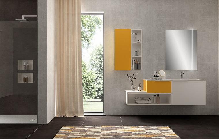 Box doccia in muratura con porta di vetro, bagno arredato con un mobile sospeso e specchio con retroilluminazione