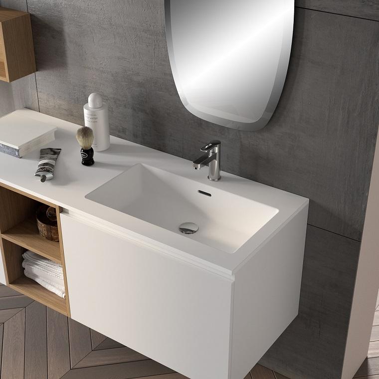 Arredamento moderno per un bagno con piastrelle di colore grigio e mobile bianco