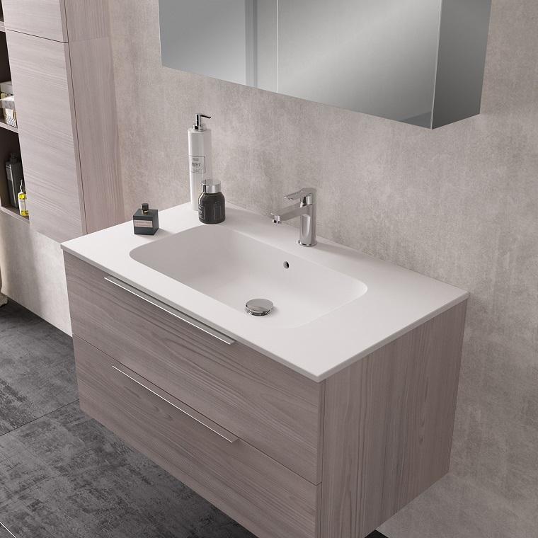 Sala da bagno arredata con un mobile di legno e lavabo da incasso, parete con piastrelle di colore grigio tonalità chiara