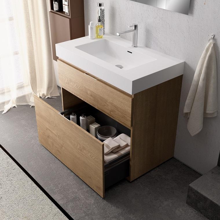 Mobile di legno con lavabo in appoggio e cassetti con maniglie di metallo