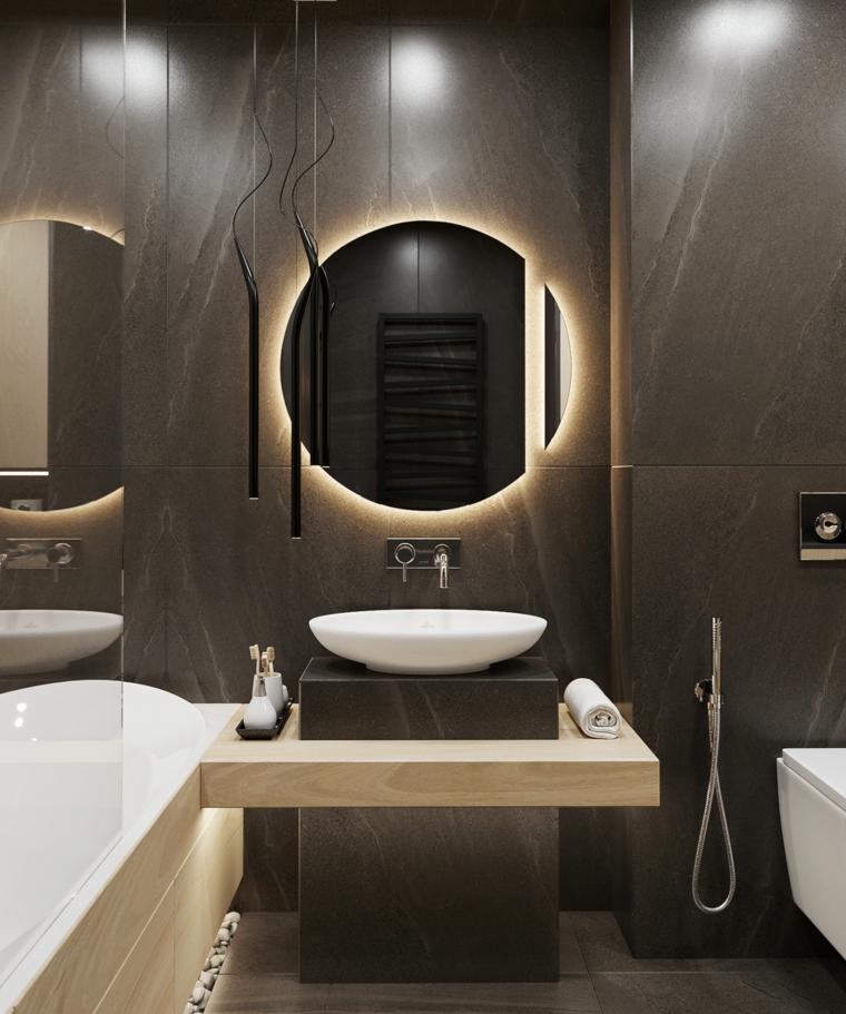 Rivestimenti bagni esempi con piastrelle di colore nero, arredamento con mobile e specchio rotondo