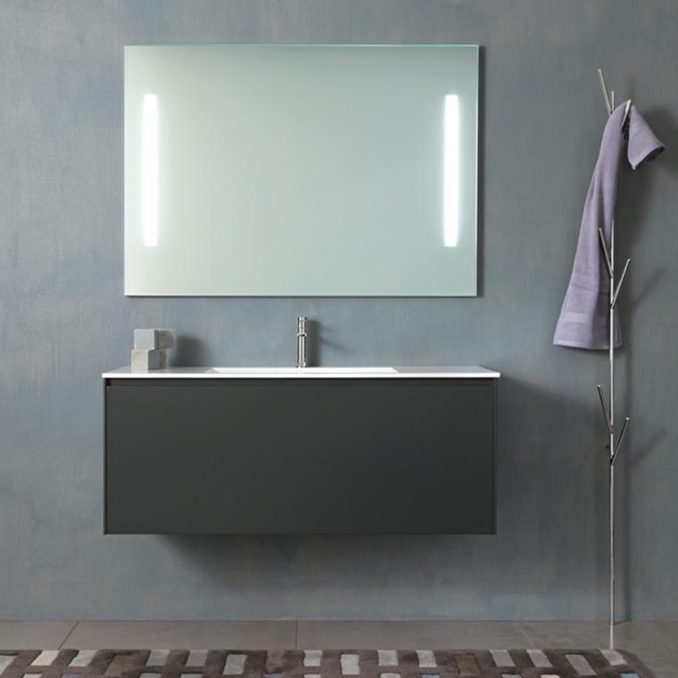 Arredare un bagno con mobile lavabo colore nero, specchio con lampade, pavimento con piastrelle e tappeto
