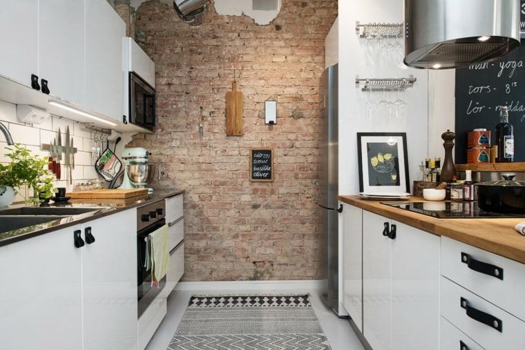cucina bianca con top in legno e nero, cappa ovale in acciaio inox e pareti rivestite in pietra per interni