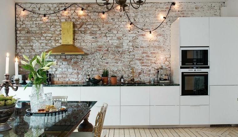 cucina bianca lineare con cappa dorata e luci appese, pareti interne in pietra e tavolo da pranzo
