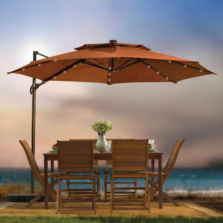 Set tavolo da pranzo con sedie abbinate in legno, ombrellone con lucine e tessuto arancione, vaso con fiori per la decorazione