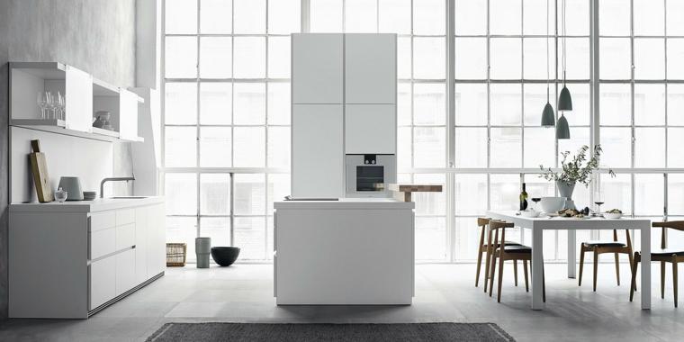 contemporaneo arredamento di un ambiente unico con cucina bianca e tavolo con sedie in legno