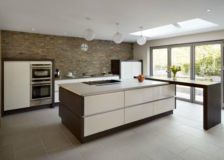 parete in muratura e cucina dal design moderno con isola e mobili bianchi e marroni