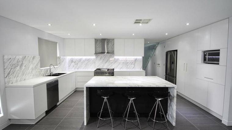 lussuosa e moderna cucina con mobili bianchi, isola, top e paraschizzi in marmo