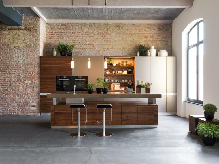 elegante open space con cucina con isola mobili in legno e sgabelli. lampadari a sospensioni, pareti riveste in pietra