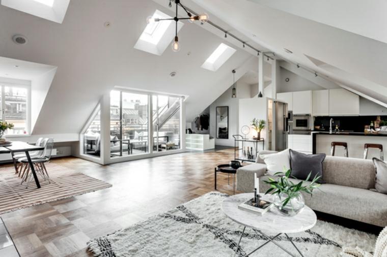 come arredare mansarda open space di ampie dimensioni con cucina e isola, tavolo da pranzo e zona living con divano grigio