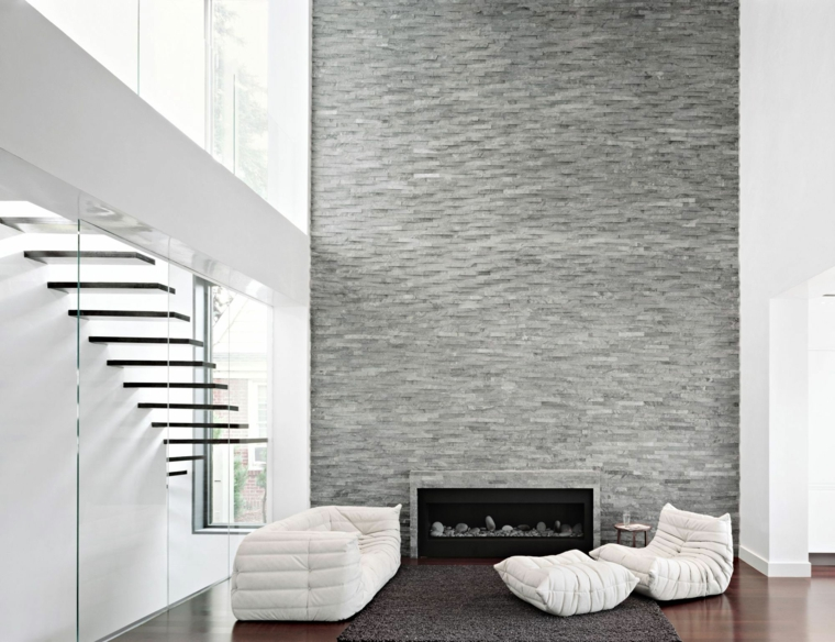 soggiorno in stile essenziale con un divano e delle poltrone bianche, un camino moderno e interni in pietra