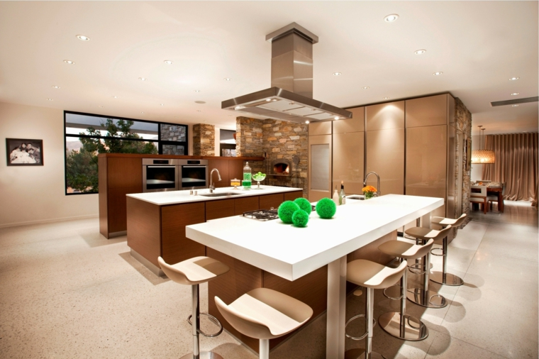 contemporanea soluzione open space con una cucina con isola e parete con doppio forno, tavolo bianco e sgabelli