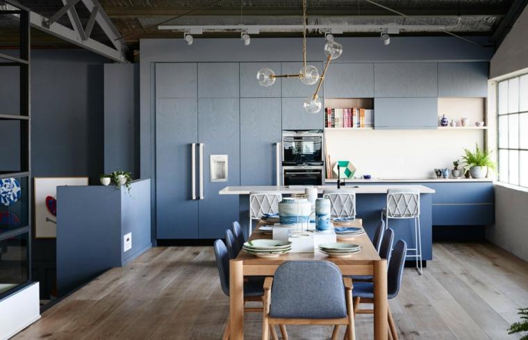cucina a vista con parete attrezzata, isola con sgabelli e tavolo per il pranzo, mobili blu chiaro