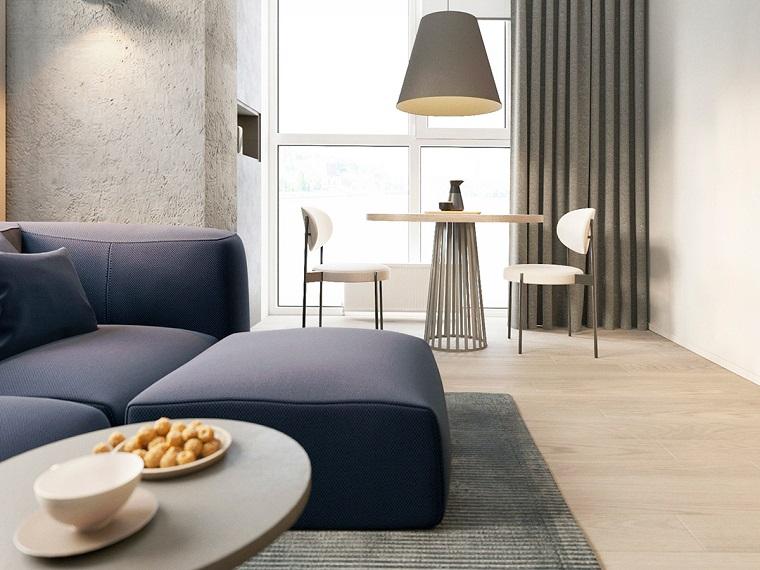 Arredare salotto e sala da pranzo insieme, divano di colore blu con tavolo di legno e due sedie