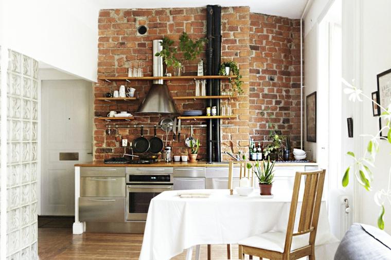 piccola cucina con mobili ed elettrodomestici in acciaio inox, mensole in legno e rivestimento parete in pietra