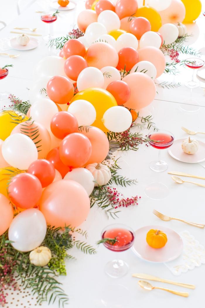 Tavolo apparecchiato, centrotavola con palloncini, bacche rosse e rametti