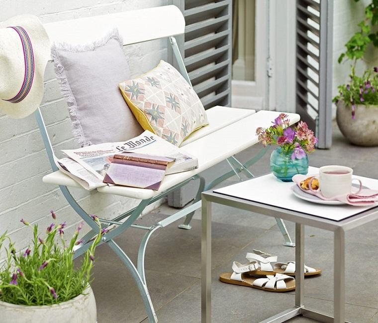 Piante ornamentali da giardino, arredamento con una panchina di ferro battuto e tavolino
