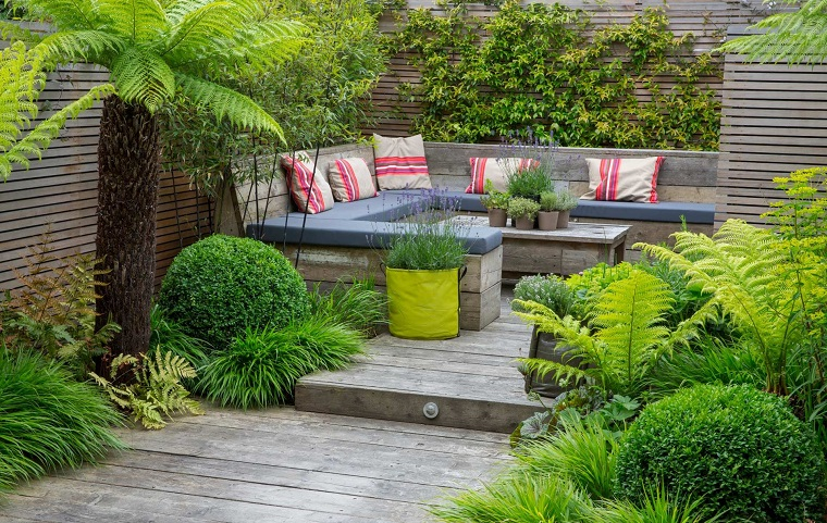 Alberi da giardino sempreverdi, arredamento con un divano di legno e cuscini colorati