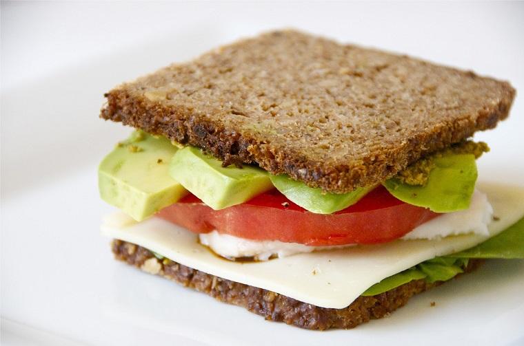 Un sandwich con pane integrale e formaggio, aggiunta di fette di avocado