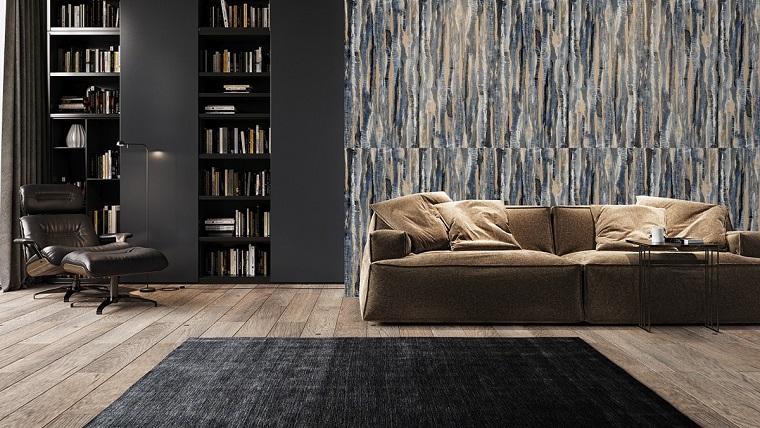 Soggiorno arredato con un divano e poltrona in pelle nera, parete decorata e libreria in cartongesso nera