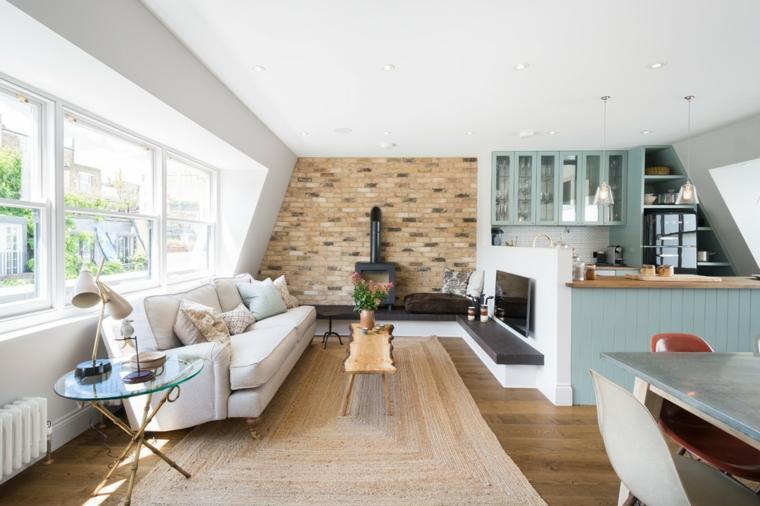open space con cucina a u divano bianco, parete con mattoni a vista e camino, divano bianco