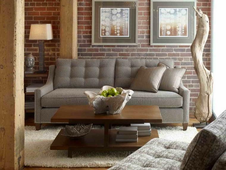 divano color tortora, parete con mattoni a vista, tavolino in legno con libri e soprammobili di design