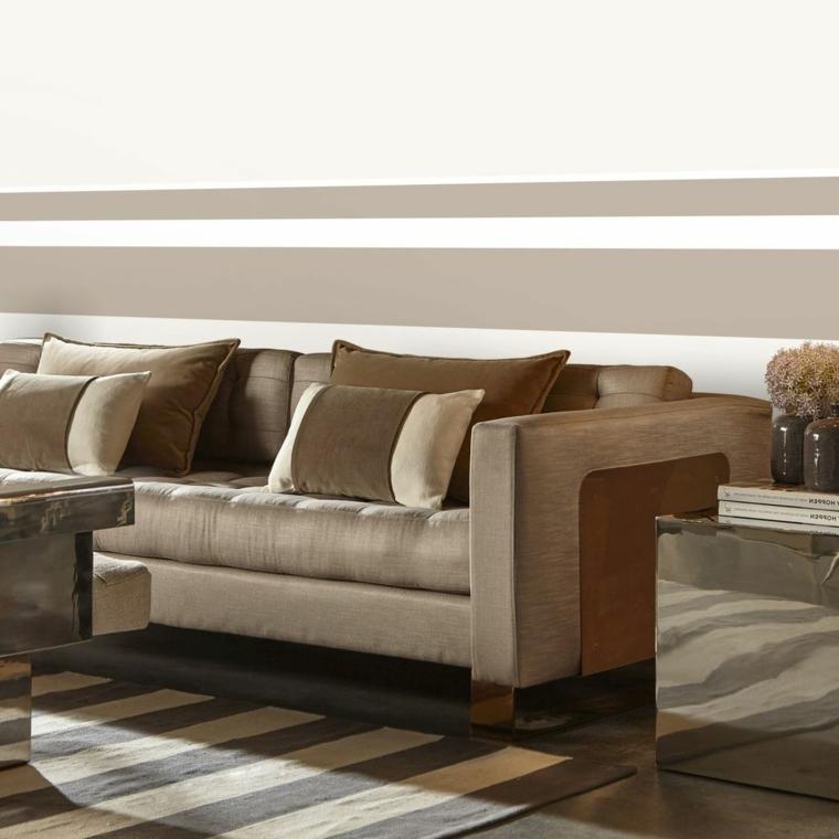 divano, cuscini e tappeto di una tonalità di colore tortora calda, parete a righe bianche e tortora