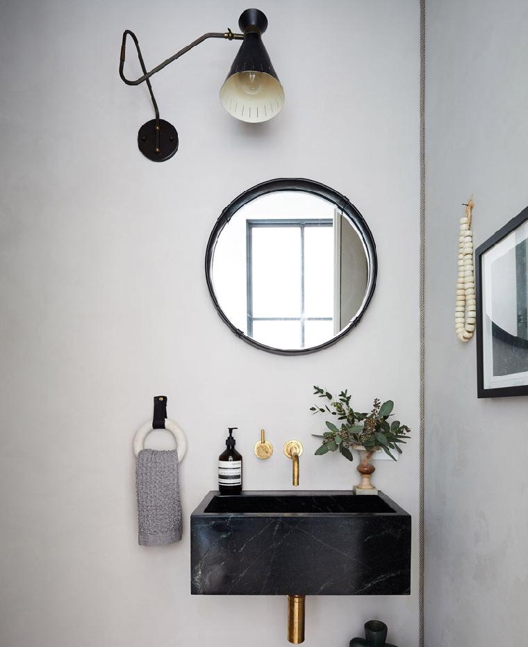 pareti grigio chiaro e scruto specchio rotondo da bagno lavandino sospeso di marmo nero