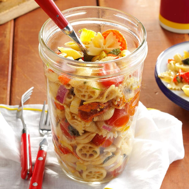 Pasta fredda di diverso tipo in un barattolo di vetro, condimento con verdure di stagione