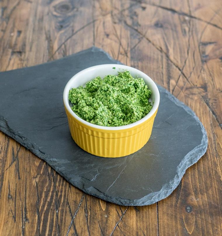 Ciotola di colore giallo su un pezzo di pietra con pesto alla genovese, ricette secondi piatti