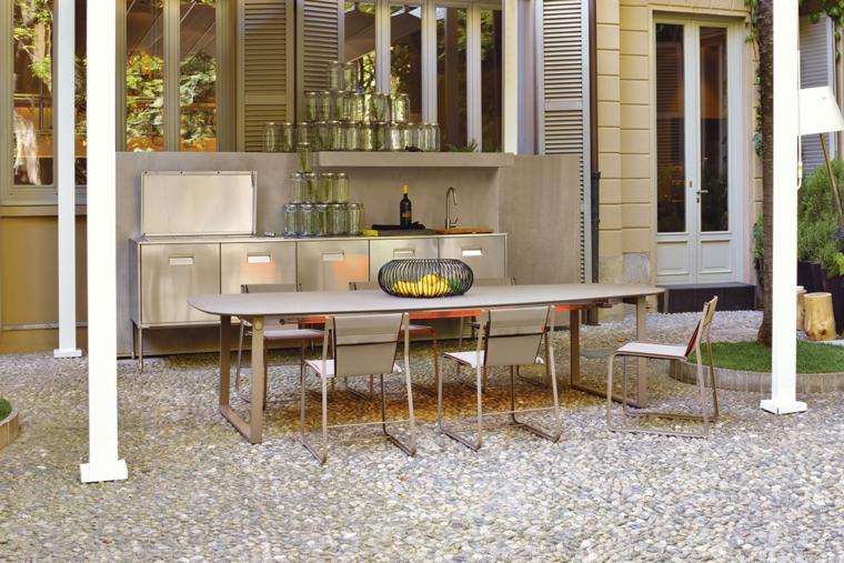 Pavimentazione giardino con ghiaia e arredamento con una cucina da esterno in acciaio inox