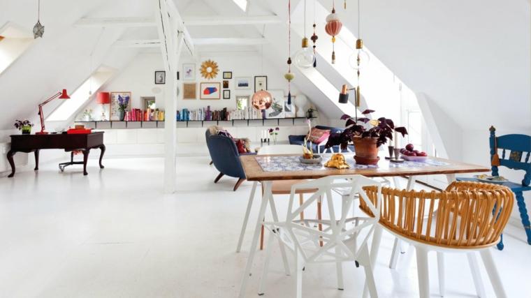 tavolo per il pranzo in legno con sedie dal design diverso, oggetti decorativi appesi al soffitto e mensole, arredare mansarda open space