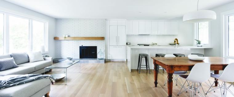 cucina a vista bianca, tavolo da pranzo in legno e divano angolare grigio chiaro
