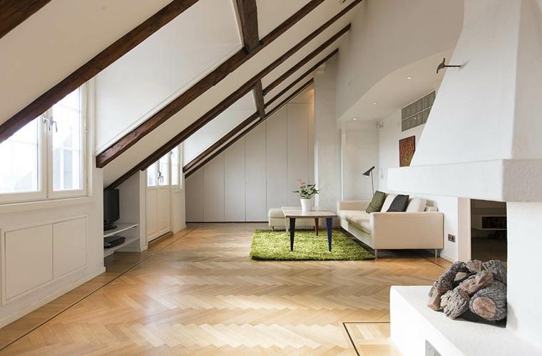 soggiorno ampio e moderno arredato con un divano bianco, camino, tavolino e tappeto verde, come arredare un attico
