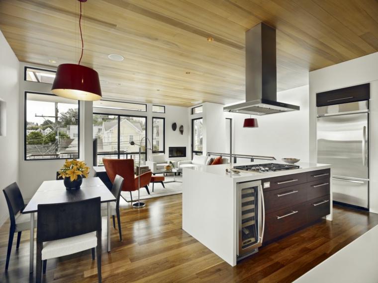 come arredare ambiente unico cucina soggiorno isola con fuochi e cappa, tavolo e poltrone bordeaux