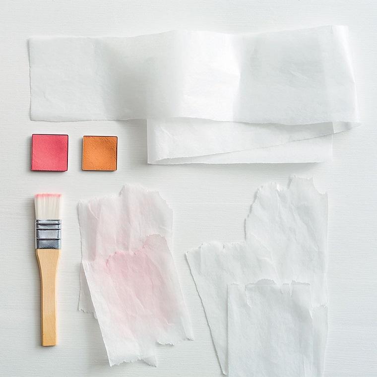Lavoretti di carta e occorrente, pennello e fogli di carta bianca sottile, piccoli pezzettini di vernice in polvere