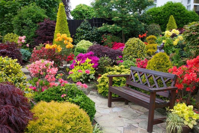 Alberi ornamentali da giardino, tanti fiori colorati e una panchina di legno colore scuro