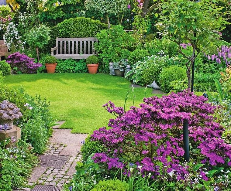 Un giardino con prato verde e tanti fiori e alberi, panchina di legno e un camminamento