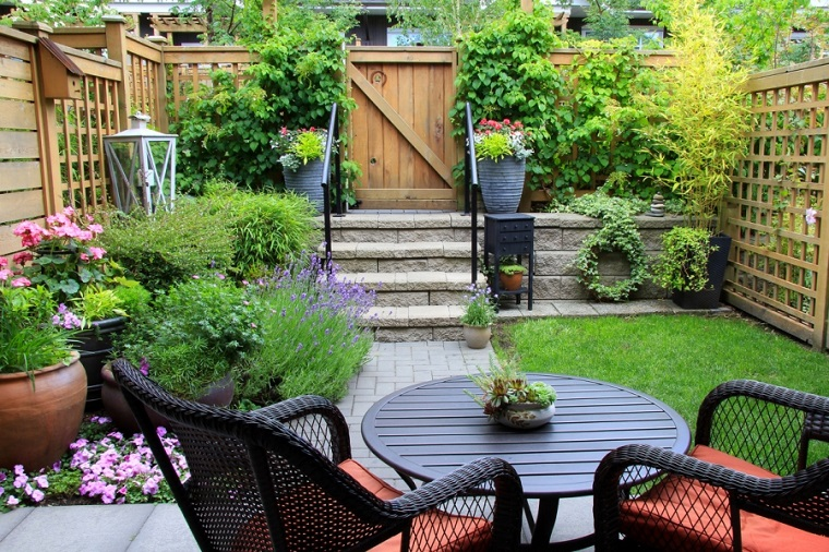 Alberi ornamentali da giardino, arredamento con un tavolo rotondo e due sedie in rattan