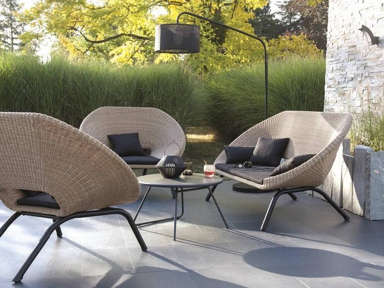 Idea di arredamento dei piccoli giardini con mobili in rattan e un tavolino rotondo di metallo