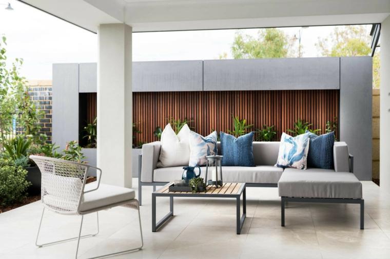 Un divano da esterno di colore grigio con tavolino basso sotto una pergola di giardino
