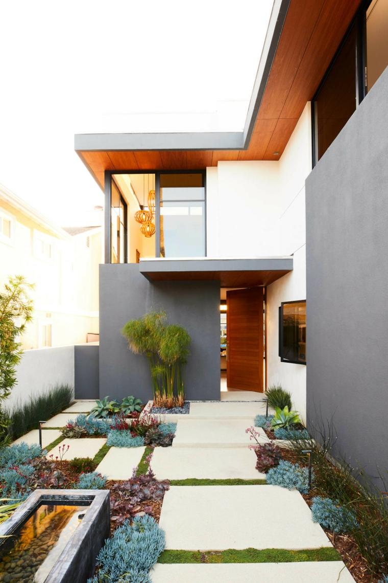Piccoli giardini con pavimentazione in cemento, piante grasse e una piccola fontana