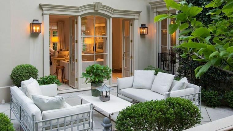 Alberi sempreverdi in un giardino piccolo con mobili in ferro battuto di colore bianco